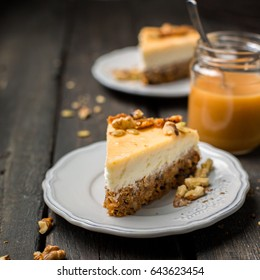Carrot nut vanilla cheesecake with salty homemade caramel on a white plate on a dark wooden vintage background. Two pieces of homemade cheesecake. Caramel sauce in a jar.