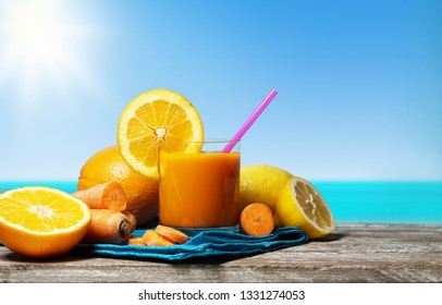 Carrot, orange and lemon juice. Healthy and refreshing fruity summer drink front view on a wooden table with blue sea and sky on background in a beautiful hot summer day.
