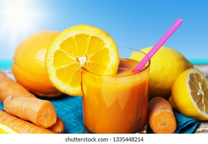Carrot, orange and lemon juice. Healthy and refreshing fruity summer drink front view closeup on a wooden table with blue sea and sky on background in a beautiful hot summer day.