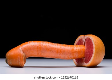 Carrot and red grapefruit as symbol of penetrative sex, physical intimacy, sexual activity metaphor