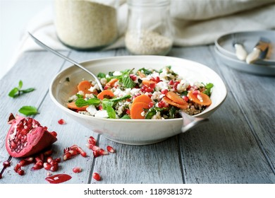 Carrot salad with a mixture of grains, mint and pomegranate. The concept of healthy,  seasonal food
