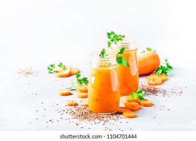 Carrot smoothie or juice with linen seeds, healthy and useful drink, gray background, selective focus