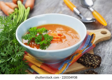 Carrot soup in blue bowl on the table