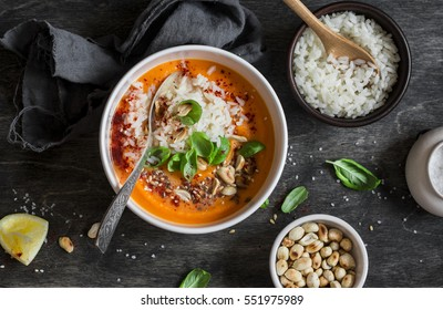 Carrot sweet potato soup with rice on the dark table, top view. Flat lay