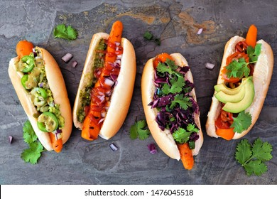 Carrot vegan hot dogs with assorted toppings. Above view scene on a dark slate background. Plant based meatless meal concept.