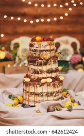 Carrot wedding naked cake with open biscuit decorated with citrus, oranges on a wooden background