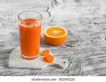 carrot-orange juice in a glass beaker on a light wooden background