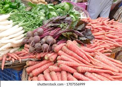 Carrots and beets displayed at an outdoor market in Varanasi, India