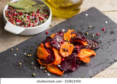 Carrots and beets . Healthy organic vegetable chips with coarse sea salt, pepper and coriander. Selective focus