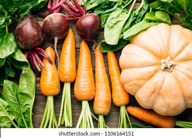 carrots, beets, spinach, pumpkin on a wooden background, cutting board and knife, fresh vegetables
