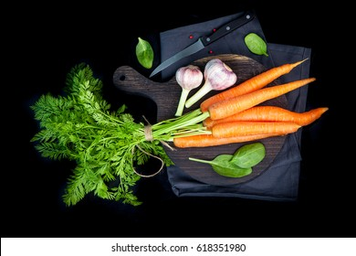 Carrots, celery and other vegetables on a dark board. Green concept. Healthy lifestyle