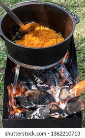 Carrots are cooking in the pot, carrots on the fire for pilaf. Camping in the nature and preparing food concept