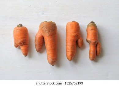 Carrots of different imperfect shapes. Ugly vegetables concept on white background with shadow