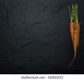 Carrots with Green Tops On a Black Slate Background Copy Space