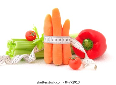 Carrots with tape measure and vegetables on the white background, concept of diet
