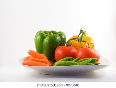 Carrots, tomatoes, green peas and two bell peppers on a white plate.