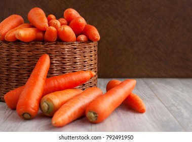 Carrots in a wicker box. A lot of carrots in a wicker basket. Carrots are stacked with a basket. Orange vegetables for diet and healthy eating. Carrots on a wooden background.