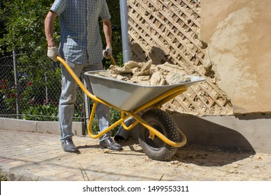to carry wheelbarrow construction debris,a man with a wheelbarrow debris near the house