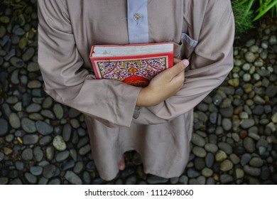 carrying the holy book of the Qur'an