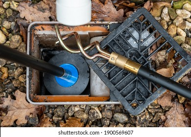 Carrying out emergency cleaning of a blocked drainage gulley outlet with a Drain rod with  plunger attachment