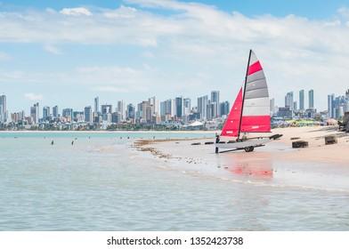 Carrying a sailing boat on a beach. Praia do Bessa beach, Joao Pessoa PB, Brazil. Beachfront buildings on background.