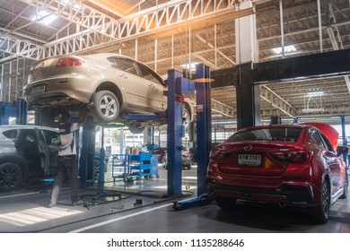 Cars are being maintained by technicians. At the Mazda service center, Amphoe Mueang Pathum Thani, Pathum Thani, Thailand. 09:53 AM, 5 July 2018.