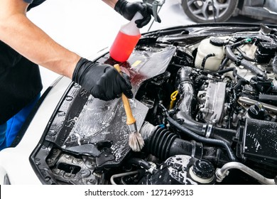 Cars in a carwash. Car wash with foam at station. Carwash. Washing at the station. Car washing concept. Car detailing. A man cleaning car. Worker cleaning. Cleaning engine with the foam and a brush