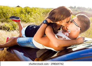 Cars - couple driving in new car smiling happy looking at camera and  kissing.Young people on road trip drive in car.Outdoor sensual couple laying on the car enjoy their trip together,casual outfit