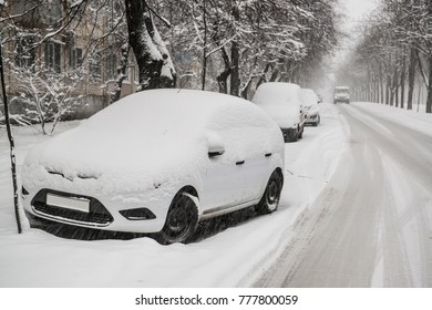 Cars covered by snow on the slippery road during heavy snowfall in town