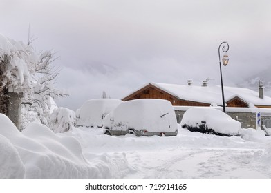 cars covered by snow parking in a village