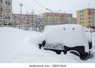 Cars covered with snow after a snowfall. Around the snowdrifts and a lot of snow on the machines. In the background multicolored panel buildings. Cold winter weather. Magadan, Siberia, Far East Russia