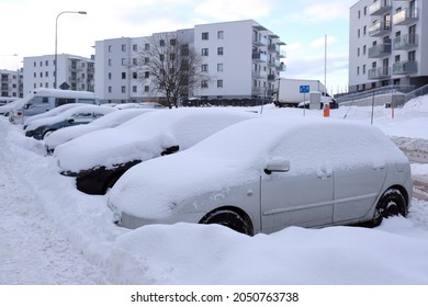 Cars covered with snow after snowstorm are standing in the street in town