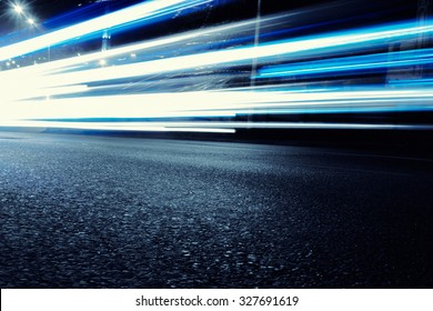 Cars create light blue light trails from their headlights as they move in a city during night time