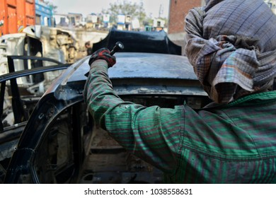 The cars are dismantled using very sharp tools, a worker uses hammer and  crowbar to rip apart the back portion of the car.