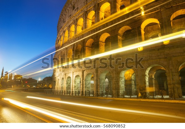 Cars drive by the Roman Colosseum in Rome, Italy.