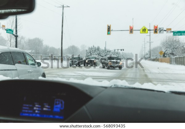 Car's driving on icy or snowy roads in an American town. Boise, Idaho, USA.