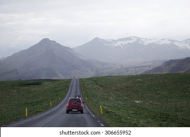 cars driving on a straigth road heading into the distance towards nearby mountains under overcast sky