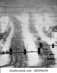 Cars driving in winter blizzard snow storm on streets in town with traffic lights