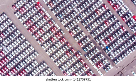 Cars export terminal in export and import business and logistics. Shipping cargo to harbor. Aerial view of a large number of  new cars lined up outside an automobile factory ready to ship over sea.