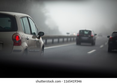 Cars going fast on a highway on a foggy autumn day