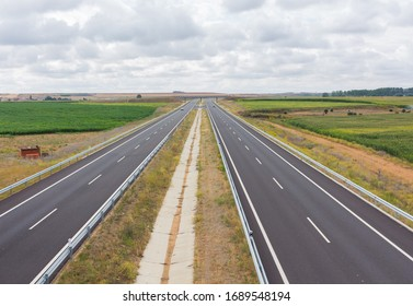 Cars in a highway among the cereal plantation fields in Spain.