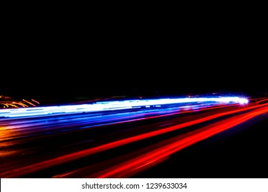 Cars light trails on a curved highway at night. Night traffic trails. Motion blur. Night city road with traffic headlight motion. Cityscape. Light up road by vehicle motion blur.
