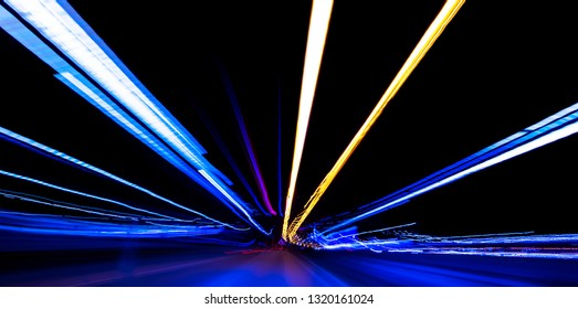 Cars light trails on a curved highway at night. Night traffic trails. Motion blur. Night city road with traffic headlight motion. Cityscape. Light up road by vehicle motion blur. Long exposure