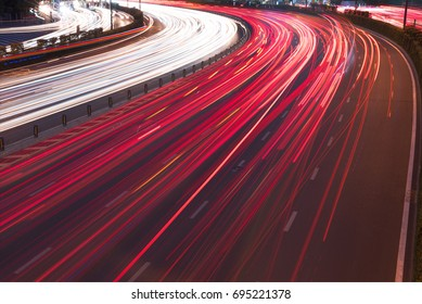 Cars light trails on a curved highway at night