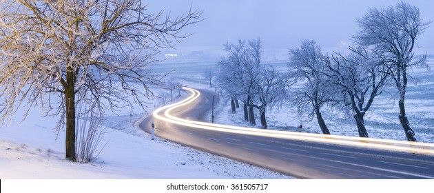 car's light trails on the road in winter morning in Czech Republic