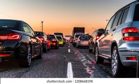 Cars in line, bumper to bumper, stuck in traffic on a busy highway.