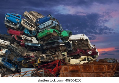 Cars lined up on each other on junkyard