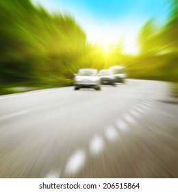 Cars in motion blur driving alone a road in the forest.
