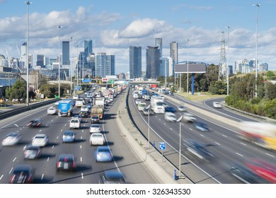Cars in motion blur in highway with skyscrapers in the background during daytime