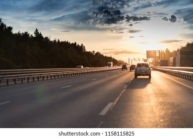 Cars in motion blur on highway during sunset. big road with metal safety barrier or rail under the cloudy blue sky and yellow and orange sun.